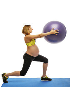 Beautiful pregnant woman doing exercises with fitball on white background