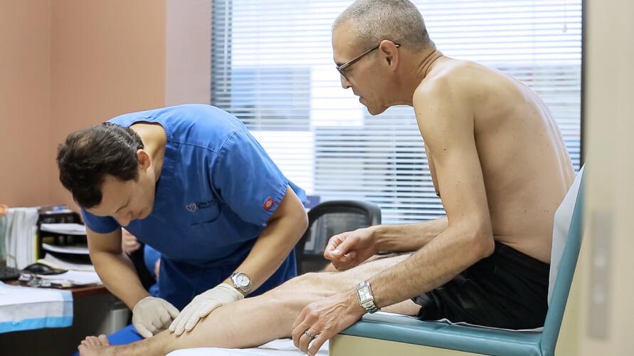 El Doctor Eddie Fernandez realiza un examen físico indoloro mientras el paciente está sentado