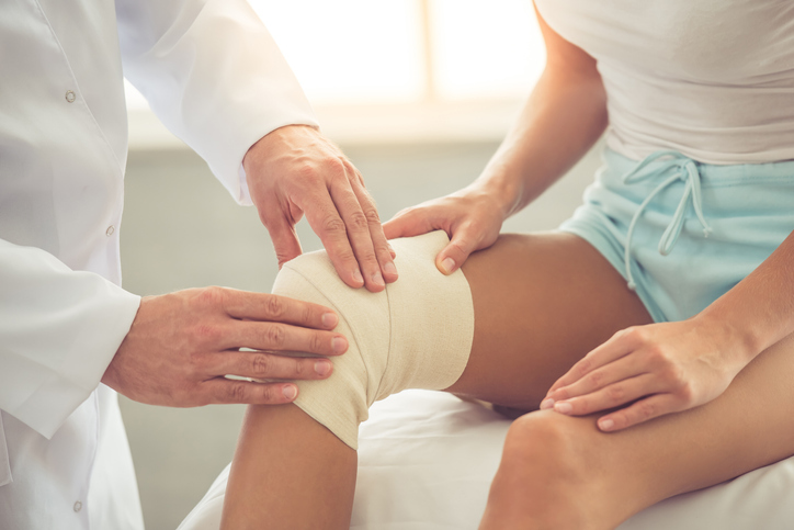 Woman getting knee examined