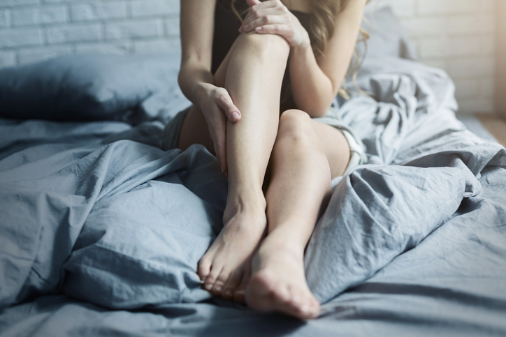 Woman in bed with restless legs