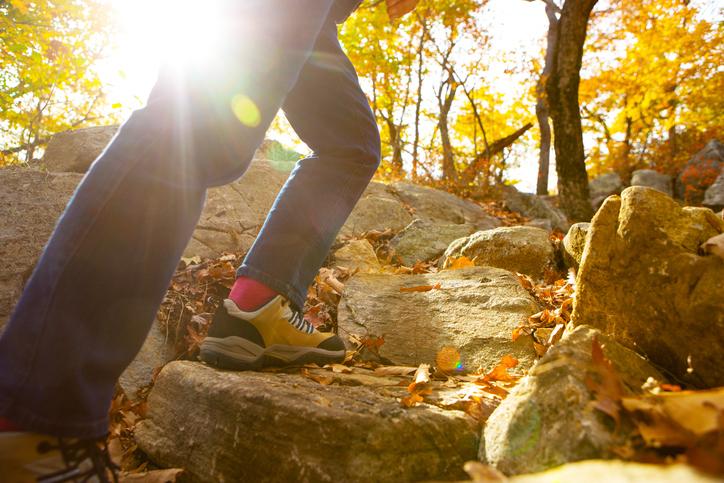 Womans legs walking up rocks in fall