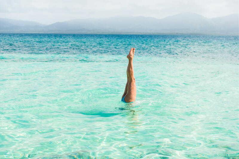 pierna sin varices haciendo el pino en el océano