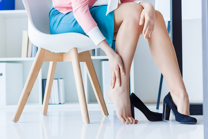 Woman sitting with leg pain